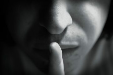 photo of person holding finger up to lips to signal quiet