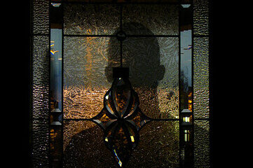 photo of a shadowy figure on the other side of a stained glass door