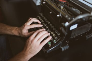 photo of hands typing on old typewriter