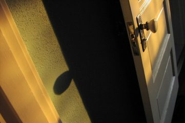 photo of a door ajar with shadowy interior