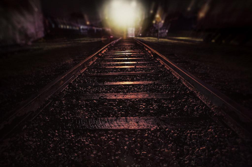 photo of train tracks at night