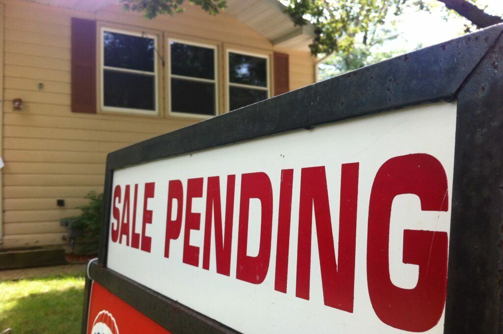"house for sale with the ""sale pending"" sign on the yard sign out front"