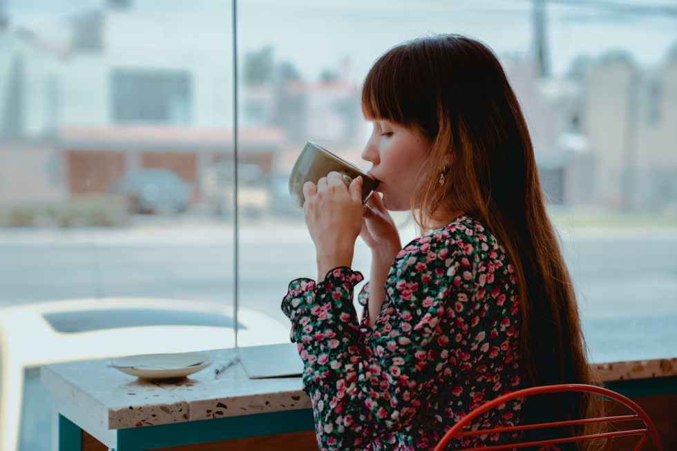 photo of woman sipping coffee