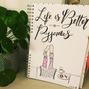 dagboek met illustraties staat op kast naast plant