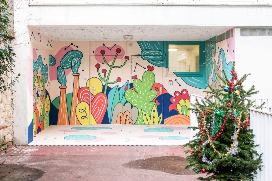 Fresque d'un personnage féminin et d'un enfant dans un univers onirique et naturel avec motifs végétaux réalisé à la crèche Bardinet à Paris