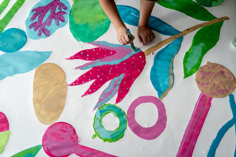 Adolescent qui peint à l'acrylique noir et couleurs avec motifs végétaux réalisée par Cécile Jaillard pendant un workshop avec le centre social Rosa Parks, Paris 19e.
