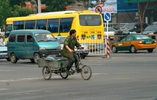 Busy city traffic with a man on a bicycle cart in the center.