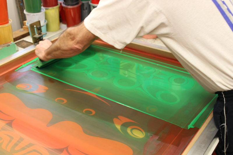 Spreading ink over a silk screen