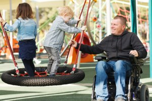 Father using power wheelchair and playing in park with children