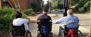 A man and a woman in manual wheelchairs hold onto the back of a man's power wheelchair for roll down a city sidewalk