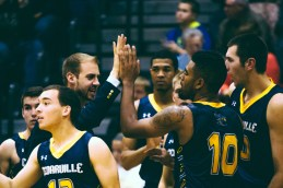 Assistant Coach Brandon Sok high fives Jason Cuffee after scoring a basket for Cedarville. (Photo: Jillian Philyaw)