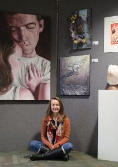 Christa Cape, a senior art major from New Hampshire, sits with her art in the Senior Showcase in the Upper SSC. Cape is one of four local college students who received the 2016 Yeck College Artist Fellowship from the Dayton Art Institute (photo: Jennifer Gammie).
