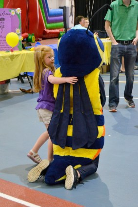 A little girl sneaks in a hug from Stinger the Yellow Jacket at the CU at the Fieldhouse event.