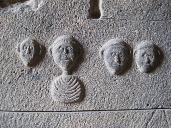 I've always been intrigued by these mysterious, oddly smiling faces sculpted on a sarcophagus.
