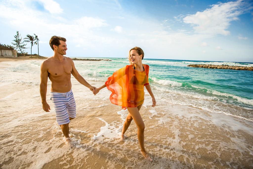 Hyatt-Zilara-Rose-Hall-Couple-Holding-Hands-Walking-Down-Beach