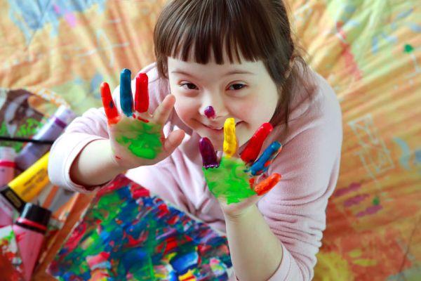 Muestra otra lado de la discapacidad, al ver una niña con Síndrome de Down con las manos pintadas de colores, disfrutando de la experiencia con una amplia sonrisa