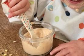 bébé mangeant avec plaisir une crème-dessert végétale fait-maison
