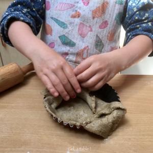 enfant qui déplie la pâte à tarte