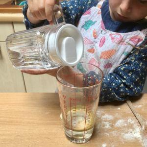enfant qui verse de l'eau dans un verre à mesurer