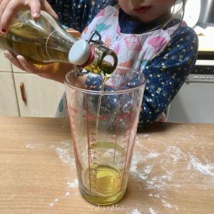enfant qui verse de l'huile d'olive dans un verre à mesurer