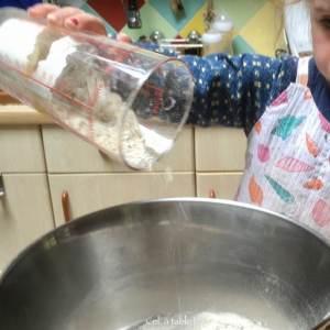 Enfant qui verse de la farine d'épeautre dans un saladier