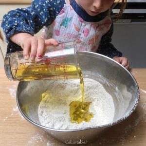 enfant qui verse de l'huile d'olive dans un saladier