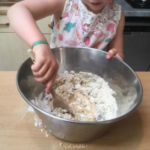 Enfant qui mélange à la cuillère une pâte à pizza