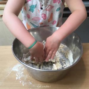 enfant qui mélange une pâte à pizza à la main
