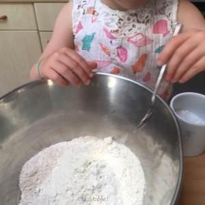 enfant qui rajoute une pincée de sel à la pâte à pizza