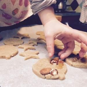enfant qui décore des biscuits avec des fruits secs