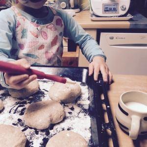 enfant qui enduit de lait les petits pains