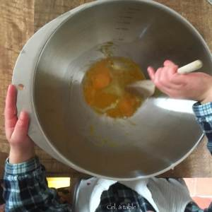 enfant qui mélange un oeuf dans un saladier