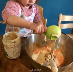 enfant qui verse de la purée d'amande dans un saladier