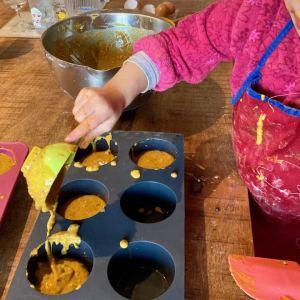 enfant qui verse de la pâte à muffins