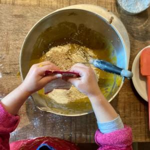enfant qui verse un sachet de sucre vanillé