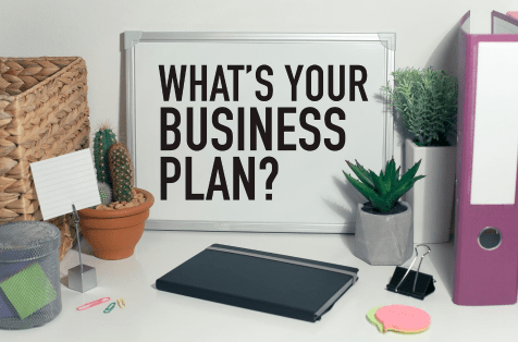 "Small whiteboard with ""What's Your Business Plan?"" written on it."