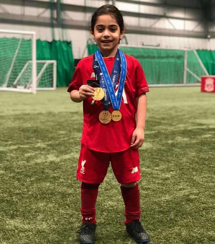 The young footballer with his gold medals on the Liverpool training field