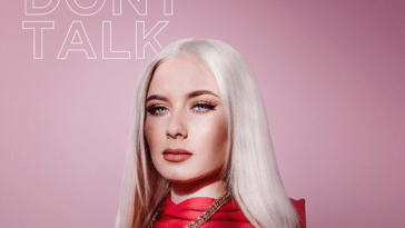 "Single cover artwork for ""We Don't Talk"" by Wiktoria, which sees her standing in a red top in front of a pink background"