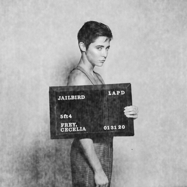 """The single artwork for CeCe's new single """"Jailbird"""" which sees CeCe turned to the side holding up a black board, similar to a mug shot."""
