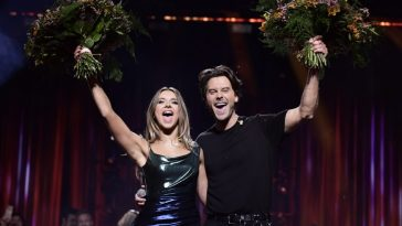 Hanna Ferm and Victor Crone celebrating their Melodifestivalen 2020 wins by holding their flowers up high.