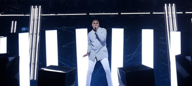 """Mohombi in white jeans and a light blue jacket performing his song """"Winners"""" on the Melodifestivalen 2020 stage."""
