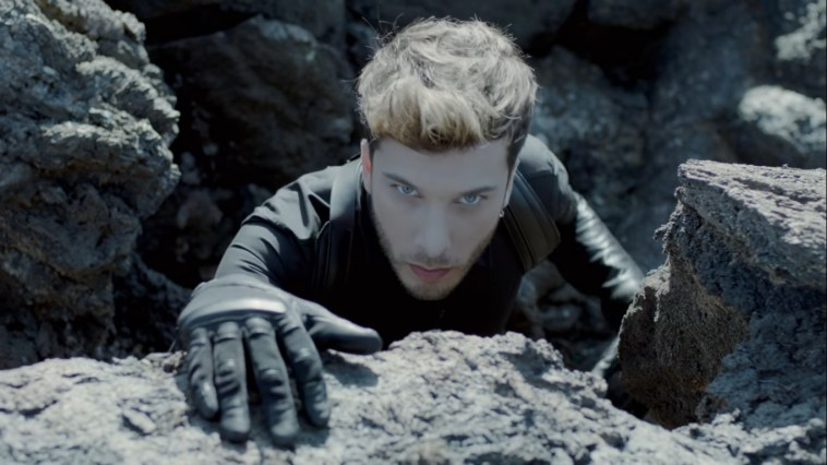 "Blas Cantó ""Universo"" still which sees him climbing a rock ledge where the camera is, with a gloved hand on the top of the rock while he stares at the camera."