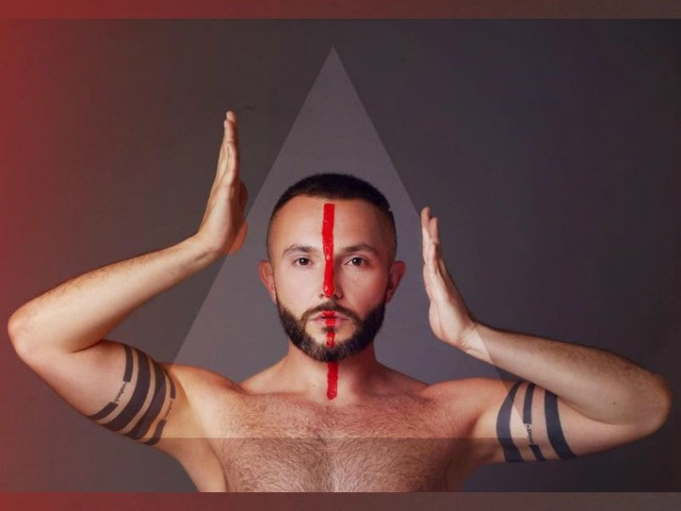 "Vasil topless with a red line down the centre of his face, with his hands on either side of his head in a promo shot for his Eurovision song ""YOU""."