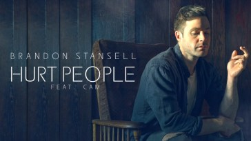 "Brandon Stansell, in promotion of new single ""Hurt People"" sitting in a wooden chair wearing a blue jacket and a white top."