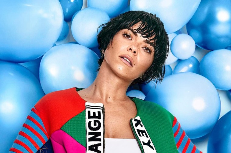 Press photo of INNA wearing a white top under a multi-coloured jacket and her short-hair wet.
