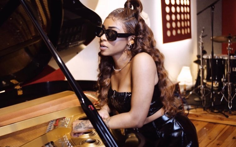 """Still from """"Liar Liar"""" music video where Relley C is wearing sunglasses and leaning against a piano."""