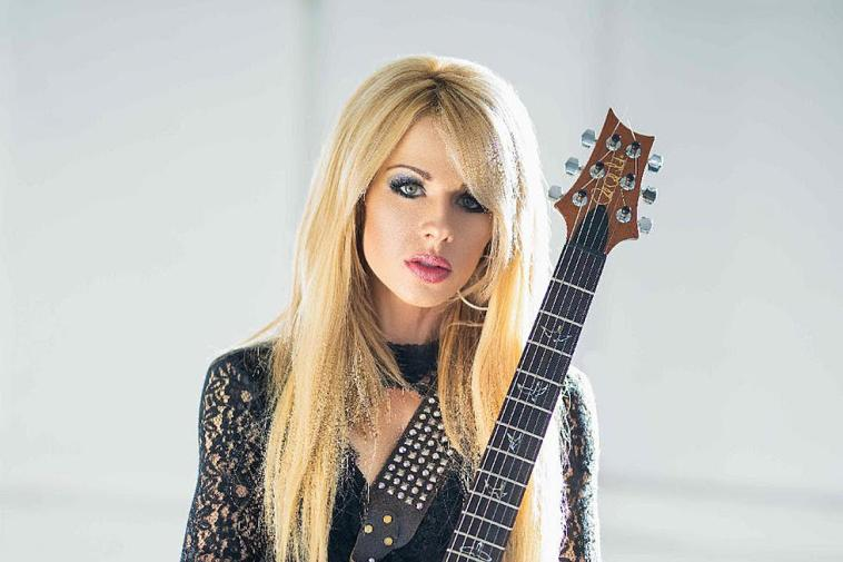 """Orianthi promo picture for """"Sinners Hymn"""" where she's wearing a black netting dress with the guitar neck across her chest."""