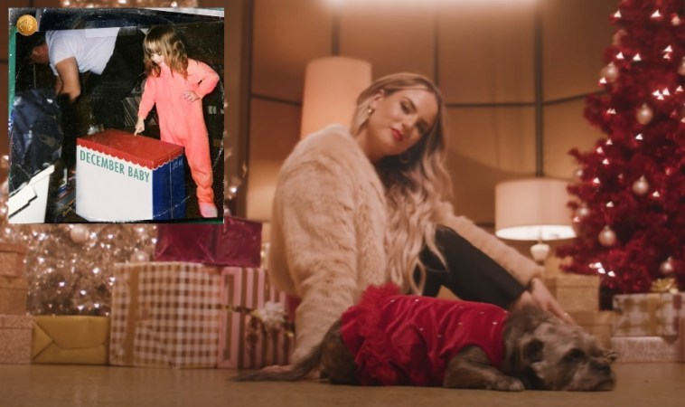 "Music video still from ""The Christmas Song"" video from last year that sees JoJo sitting in front of the camera wearing black jeans and a cream coloured jacket and a red blanket over one leg, sitting on the floor with her blonde hair over one shoulder, looking at the camera, with presents stacked up against her back with a gold Christmas tree behind whilst an image in the top left corner showing the album artwork for ""December Baby"" which shows JoJo as a child in a pink jumpsuit opening a Christmas box with her dad behind her."