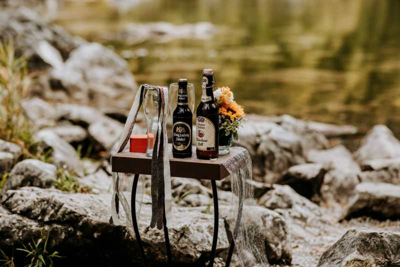 photo of two bottles of beer and a handfasting cord at an outdoor wedding for a symbolic ceremony