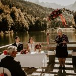A raft floating on a lake with a bride and groom and their wedding celebrant